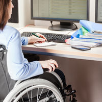 Invalid or disabled woman sitting wheelchair working office desk computer