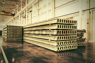 Stack of precast reinforced concrete slabs in a house-building factory workshop