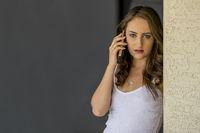 Concerned Brunette Model At Home With Mobile Device
