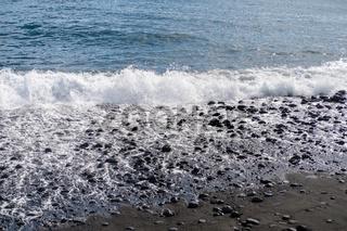 ocean water on black sand
