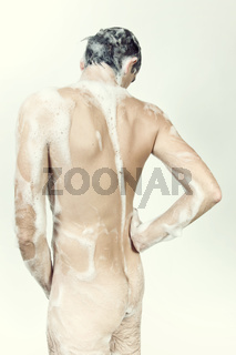 Young naked man taking a shower in the foam with a beautiful body