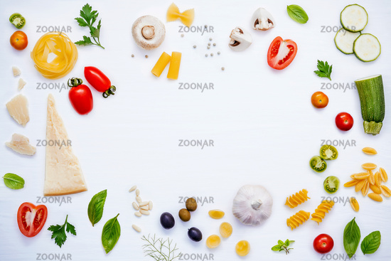 Italian food concept .Various kind of pasta with ingredients sweet basil ,tomato ,garlic ,parsley ,bay leaves ,pepper ,champignon,zucchini and parmesan cheese on white wooden background flat lay.