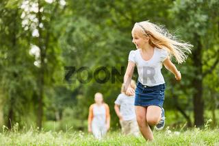 Blondes Mädchen läuft über eine Wiese