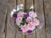 Glasschale mit Blumen auf Gartentisch