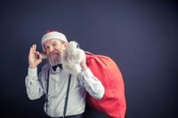Santa Claus holding red bag with presents.