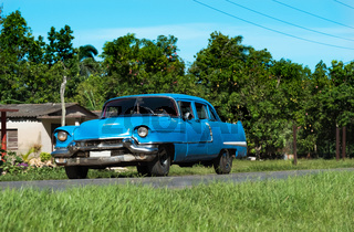 Amerikanischer blauer Oldtimer fährt auf der Landstrasse in Matanzas Cuba - Serie Cuba Reportage