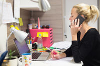 Female entrepreneur talking on mobile phone in colorful modern creative working environment.