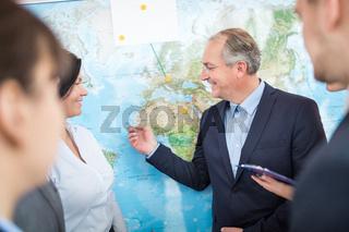 Älterer Geschäftsmann vor einer Weltkarte