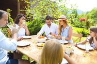 Family dinner variety of Italian dishes on wooden table in the garden