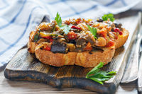 Piece of grilled bread with baked vegetables.