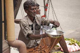Verkäufer mit Waage auf dem Markt in Galle