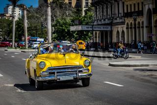 Amerikanischer gelber Cabriolet Oldtimer mit Touristen in Havanna Kuba