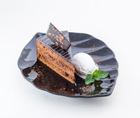 Piece of chocolate cake with ice cream and mint
