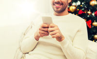 smiling man with smartphone at home for christmas