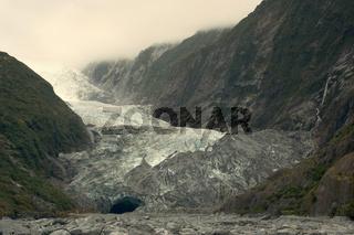 Franz Josef Gletscher, Fluss aus Eis frisst sich durch das Gletschertal umgeben von Bergen, die von rspruenglichem gemaessigtem Regenwald bedeckt sind. Waehrend viele Gletscher weltweit auf dem Rueckzug sind, fliesst der Franz Josef und sein Nachbar, der