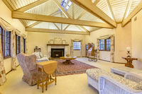 Bright, open and warm living room with vaulted ceilings and rug