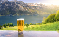 Glass of beer in a summer alpine scenery