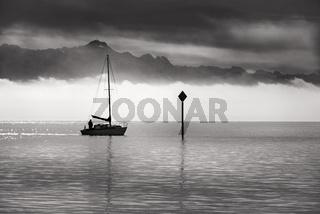 Monochrome image of a single boat sailing