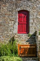 Ancient stone house with a wooden barrier and a red door