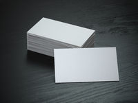 White blank business cards mockup on black wood table background,