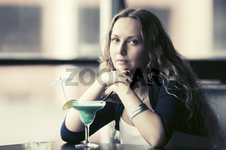 Sad young beautiful woman with cocktail at restaurant
