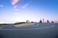 empty sharp turn road with modern city