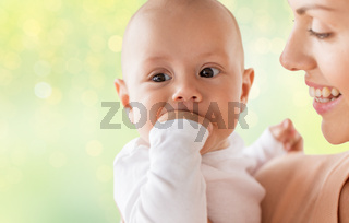 happy mother with little baby boy sucking fingers