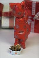 Katze in Geschenkpapier mit weihnachtlichem Katzennapf