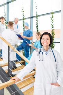 Ältere Frau als Chefarzt vor ihrem Ärzteteam