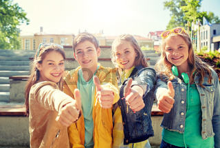 happy students or friends showing thumbs up