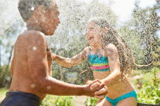 Mädchen und Junge plantschen mit Wasser