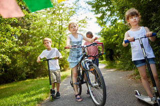 Kinder mit Fahrrad und Roller