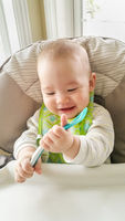 Adorable Chinese and Caucasian Baby Boy Playing With His Spoon Sitting in High Chair