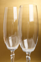 Two flutes with champagne on golden background
