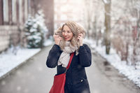 Smiling young woman walking along a snowy road