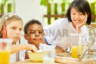 Multikulturelle Gruppe Kinder frühstückt zusammen