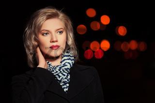 Fashion blond woman in black coat walking in a night city street