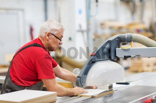 carpenter with panel saw and fibreboard at factory