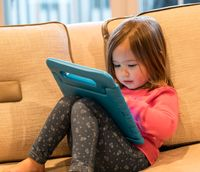 Preschool girl using a tablet computer at home