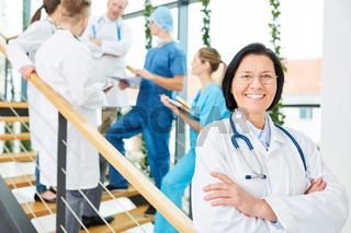 Ältere Frau als kompetente Ärztin mit Team