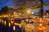 Amterdam cafe tables, canal, bridge and medieval houses in the e