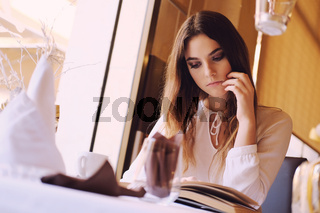 Young brunette reading a book in a restaurant