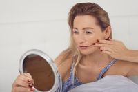 Woman looking in the mirror at her facial wrinkles
