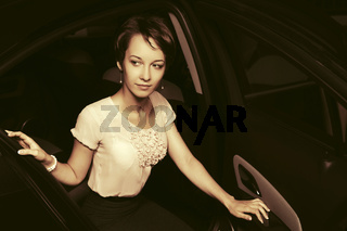 Young fashion woman sitting in a car