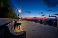 Empty bench on a seaside promenade at dusk