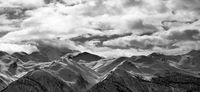 Black and white panoramic view on snowy mountains and cloudy sky in evening