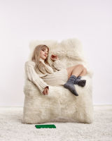 Blonde woman is sleeping in furry arm-chair
