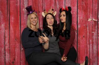 3 freche mädchen vor einer fotobox mit rotem hintergrund