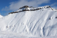 Snowy slope for freeride with traces of ski, snowboard and avalanches