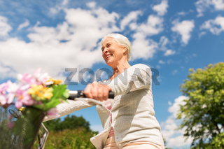 happy senior woman riding bicycle at summer park